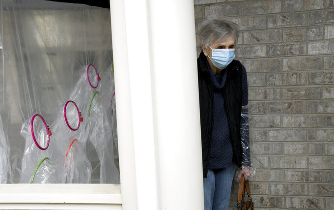 """Lynda Hartman, 75, leaves after visiting her 77-year-old husband, Len Hartman, who suffers from dementia at a """"hug tent"""" set up outside the Juniper Village assisted living center in Louisville, Colo., Wednesday, Feb. 3, 2021. The tent includes a construction-grade plastic barrier with built-in plastic sleeves to prevent the spread of the coronavirus. He has been living at the center for about a year, and the couple had not had any physical contact for at least eight months. (AP Photo/Thomas Peipert)"""