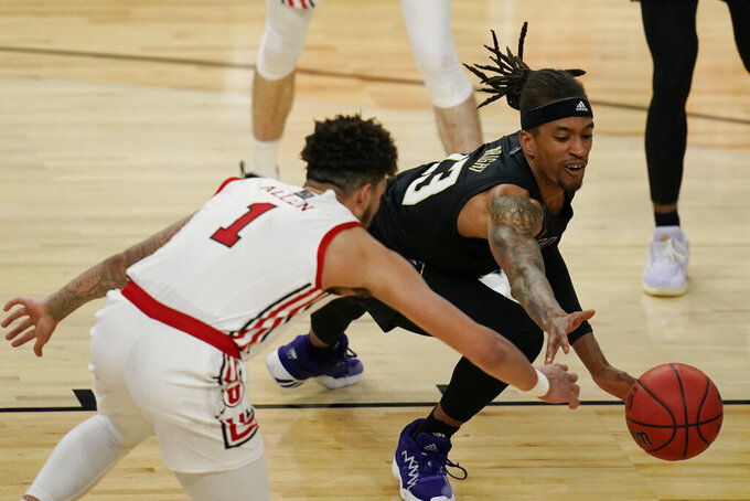 Utah's Timmy Allen (1) and Washington's Hameir Wright (13) vie for the ball during the second half of an NCAA college basketball game in the first round of the Pac-12 men's tournament Wednesday, March 10, 2021, in Las Vegas. (AP Photo/John Locher)