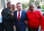 FILE- In this Jan. 11, 2019, file photo, suspended Broward County Sheriff Scott Israel, center, leaves a news conference surrounded by supporters in Fort Lauderdale, Fla., after new Florida Gov. Ron DeSantis suspended him, over his handling of last February's massacre at Marjory Stoneman Douglas High School. Before the shooting, Israel had changed his department's policy to say deputies