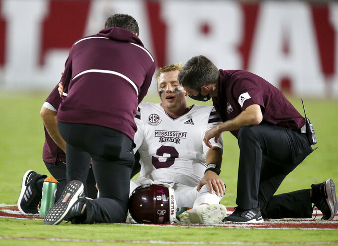 Trainers assist Mississippi State quarterback K.J. Costello (3) after he suffered an injury while during an NCAA college football game against Alabama on Saturday, Oct. 31, 2020, in Tuscaloosa, Ala. (Gary Cosby Jr./The Tuscaloosa News via AP)