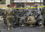 Lebanese army soldiers inspect a car that was destroyed in a bombing, in the southern port city of Sidon, Lebanon, Sunday, Jan 14, 2018. The Lebanese military said the bomb went off in a car in southern Lebanon, wounding its Palestinian owner. It was not immediately clear who carried out Sunday's bombing in the city of Sidon or why the Palestinian, identified as Mohammed Hamdan, was targeted. (AP Photo/Mohammed Zaatari)