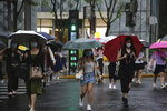 Residents using umbrellas cross an intersection in Shanghai, China, Tuesday, Sept. 14, 2021. Flights and train service were being canceled in Shanghai, China's largest city, as Typhoon Chanthu moved up the mainland coast Monday after bringing heavy rain and wind to Taiwan. (AP Photo/Chen Si)