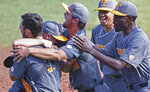 Tennessee pitcher Redmond Walsh, second from left,is mobbed by teammates after an NCAA college baseball super regional game against LSU, Sunday, June 13, 2021, in Knoxville, Tenn. (AP Photo/Wade Payne)