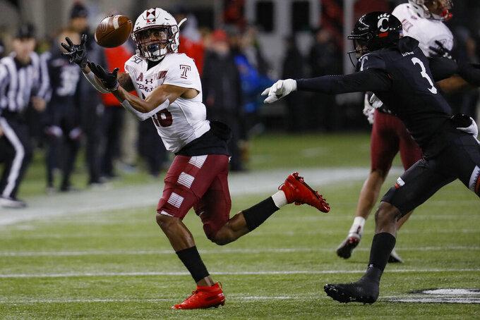 Temple wide receiver Jadan Blue, left, catches a pass against Cincinnati safety Ja'von Hicks (3) during the first half of an NCAA college football game, Saturday, Nov. 23, 2019, in Cincinnati. (AP Photo/John Minchillo)