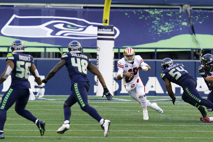 San Francisco 49ers quarterback Jimmy Garoppolo, second from right tries to scramble away from a sack by Seattle Seahawks middle linebacker Bobby Wagner (54) during the first half of an NFL football game, Sunday, Nov. 1, 2020, in Seattle. (AP Photo/Elaine Thompson)