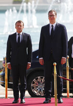 French President Emmanuel Macron, left, and Serbian President Aleksandar Vucic listen to the national anthems during a welcome ceremony in Belgrade, Serbia, Monday, July 15, 2019. French President Emmanuel Macron is for a two days official visit in Belgrade. (AP Photo/Darko Vojinovic)