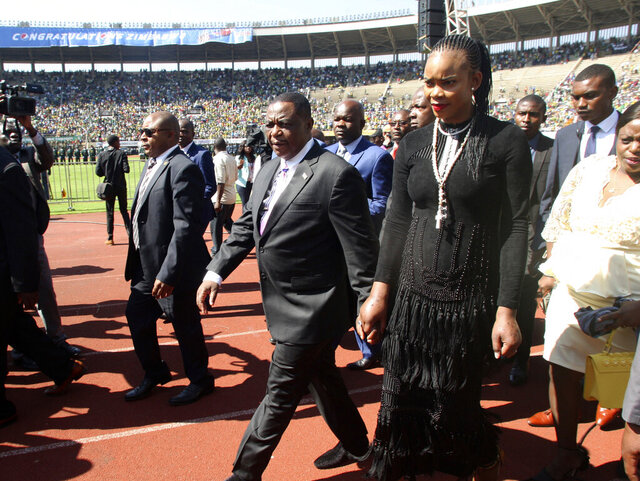 FILE — In this Sunday, Aug. 26, 2018 file photo Zimbabwean Deputy President Constantino Chiwenga is seen with his wife Marry, right, upon arrival for the inauguration ceremony of President Emmerson Mnangagwa, at the National Sports Stadium in Harare.  Marry Chiwenga has been charged with attempting to kill her husband and has also been charged with money laundering and fraud. (AP Photo/Wonder Mashura, File)