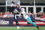 New England Patriots quarterback Mac Jones (10) unloads a pass while pressured by Miami Dolphins outside linebacker Jerome Baker (55) during the second half of an NFL football game, Sunday, Sept. 12, 2021, in Foxborough, Mass. (AP Photo/Steven Senne)