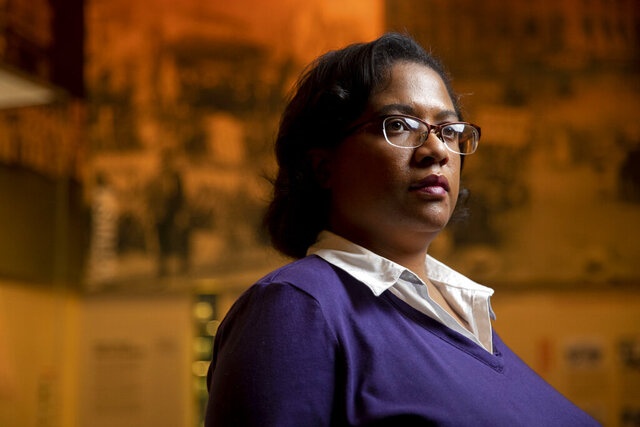 Noelle Trent, who serves as the director of interpretation, collections and education at the National Civil Rights Museum, poses for a photo Tuesday, Nov. 17, 2020, in Memphis, Tenn., in the museum's combating Jim Crow gallery. (Max Gersh/The Commercial Appeal via AP)