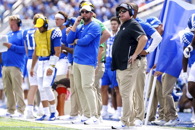 Kentucky head coach Mark Stoops, right, watches his team on the video board during the first half of an NCAA college football game against Louisiana-Monroe in Lexington, Ky., Saturday, Sept. 4, 2021. (AP Photo/Michael Clubb)
