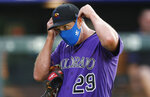 Colorado Rockies relief pitcher Bryan Shaw puts on his face mask after taking part in drills during the team's baseball practice in Coors Field, Friday, July 10, 2020, in Denver. (AP Photo/David Zalubowski)