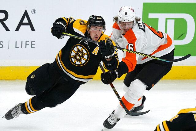 Boston Bruins center Brad Marchand (63) and Philadelphia Flyers defenseman Travis Sanheim (6) skate for position during the third period of an NHL hockey game Thursday, Jan. 21, 2021, in Boston. (AP Photo/Elise Amendola)
