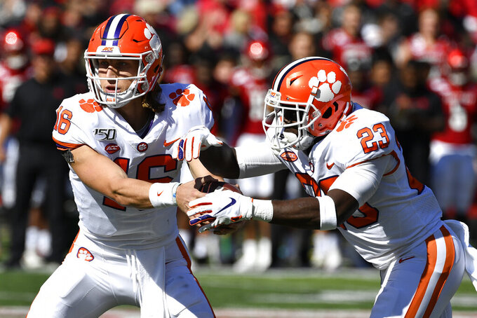 Clemson quarterback Trevor Lawrence (16) hands the ball off to running back Lyn-J Dixon (23) during the first half of an NCAA college football game against Louisville in Louisville, Ky., Saturday, Oct. 19, 2019. (AP Photo/Timothy D. Easley)