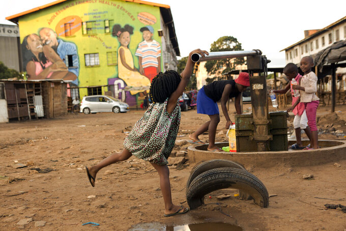 Children fetch water from a borehole in Harare, Zimbabwe, Thursday, April 2, 2020. Zimbabwe went into a lockdown for 21 days in an effort to curb the spread of the coronavirus. The new coronavirus causes mild or moderate symptoms for most people, but for some, especially older adults and people with existing health problems, it can cause more severe illness or death. (AP Photo/Tsvangirayi Mukwazhi)