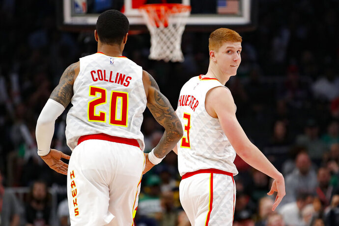 Atlanta Hawks guard Kevin Huerter (3) reacts with forward John Collins (20) after shooting a three pointer in the second half of an NBA basketball game against the Boston Celtics on Monday, Feb. 3, 2020, in Atlanta. (AP Photo/Todd Kirkland)