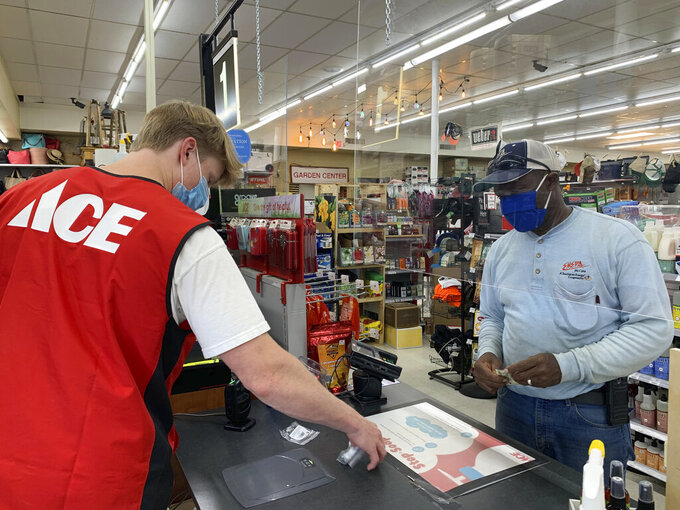 In this Thursday, June 4, 2020 photo, plexiglassinstalled to prevent the spread of COVID-19separates cashier William Majure and customer Angelo Lewis at Broadmoor Ace Hardware in Meridian. Miss. Businesses around the state are adjusting to new guidelines during the COVID-19 pandemic. (Erin Kelly/The Meridian Star via AP)