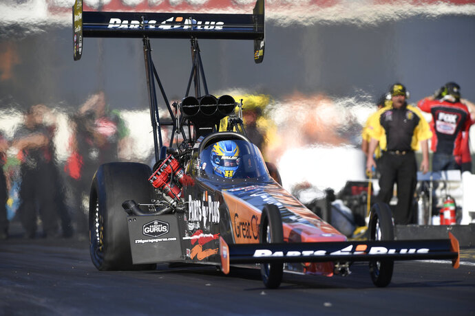 In this photo by NHRA, Clay Millican takes part in Top Fuel qualifying at the Lucas Oil NHRA Winternationals at Auto Club Raceway on Friday, Feb. 9, 2018, in Pomona, Calif. His run of 3.694 seconds at 327.74 mph posted during the second qualifying session was the best on the day. (Marc Gewertz/NHRA via AP)