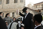 An ultra-Orthodox Jewish man swings a chicken over his family's heads as part of the Kaparot ritual in Jerusalem, Wednesday, Sept. 23, 2020. Observant Jews believe the ritual transfers one's sins from the past year into the chicken, and is performed before the Day of Atonement, Yom Kippur, the holiest day in the Jewish year, which takes place this year during a nationwide three-week lockdown to curb the spread of the coronavirus. (AP Photo/Maya Alleruzzo)