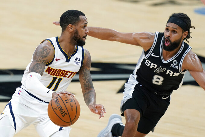 Denver Nuggets guard Monte Morris (11) drives around San Antonio Spurs guard Patty Mills (8) during the second half of an NBA basketball game in San Antonio, Friday, Jan. 29, 2021. (AP Photo/Eric Gay)