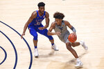 West Virginia guard Miles McBride (4) is defended by Kansas guard Ochai Agbaji (30) during the first half of an NCAA college basketball game Saturday, Feb. 6, 2021, in Morgantown, W.Va. (AP Photo/Kathleen Batten)