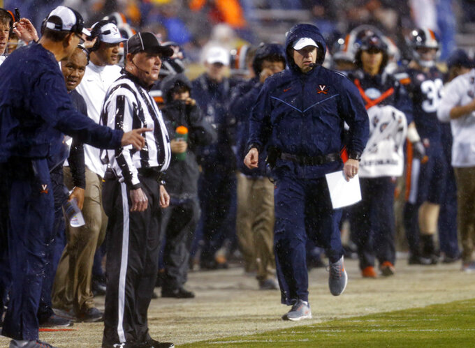 Virginia coach Bronco Mendenhall runs down the sideline during the first half of the team's NCAA college football game against Pittsburgh in Charlottesville, Va., Friday, Nov. 2, 2018. (AP Photo/Steve Helber)