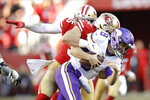 Minnesota Vikings quarterback Kirk Cousins (8), is tackled by San Francisco 49ers defensive end Nick Bosa, center, during the second half of an NFL divisional playoff football game, Saturday, Jan. 11, 2020, in Santa Clara, Calif. (AP Photo/Ben Margot)
