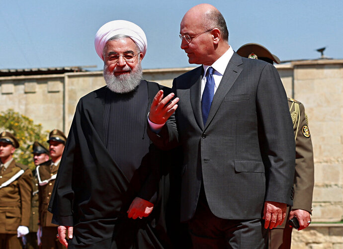 FILE - In this March 11, 2019 file photo, Iraqi President Barham Salih, right, walks with visiting Iranian President Hassan Rouhani, before their meeting at Salam Palace in Baghdad, Iraq. Iraq is seeking to reclaim a leadership role in the Arab world after decades of conflict. It is focusing on a centrist policy and its top leaders are determined to maintain good relations with both Iran and the United States. (AP Photo/Khalid Mohammed, File)
