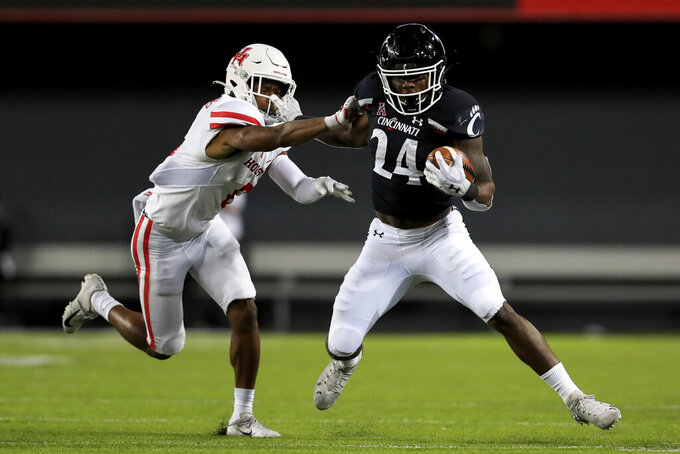 Houston cornerback Damarion Williams, left, is stiff-armed by Cincinnati running back Jerome Ford, right, during the second half of an NCAA college football game, Saturday, Nov. 7, 2020, in Cincinnati. (AP Photo/Aaron Doster)