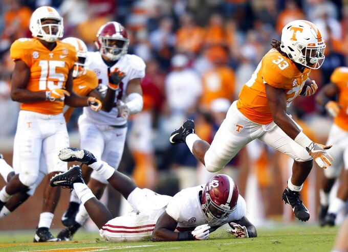 Tennessee running back Jeremy Banks (33) leaps as he escapes the grasp of Alabama linebacker Jaylen Moody (42) in the first half of an NCAA college football game Saturday, Oct. 20, 2018, in Knoxville, Tenn. (AP Photo/Wade Payne)