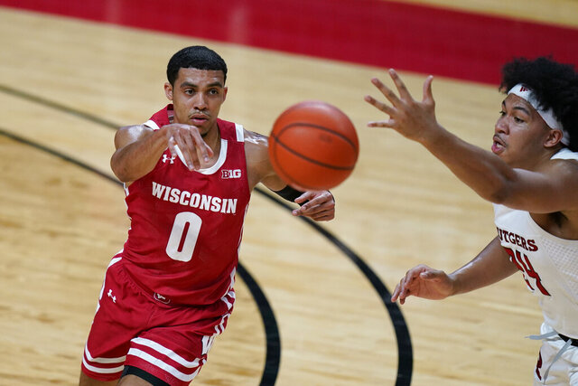 Wisconsin's D'Mitrik Trice, left, passes the ball past Rutgers' Ron Harper Jr. during the first half of an NCAA college basketball game Friday, Jan. 15, 2021, in Piscataway, N.J. (AP Photo/Seth Wenig)