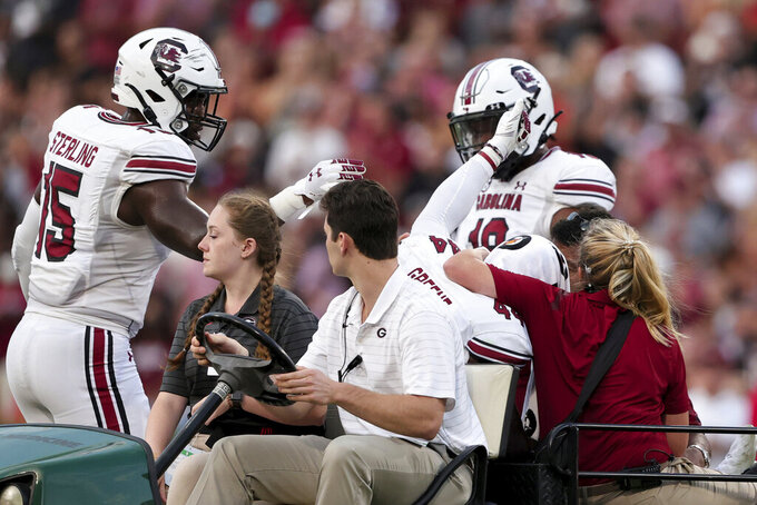 South Carolina defensive end Aaron Sterling (15) talks with linebacker Sherrod Greene (44), who gives a thumbs-up while being carted off the field after an injry during the first half of the team's NCAA college football game against Georgia on Saturday, Sept. 18, 2021, in Athens, Ga. (AP Photo/Butch Dill)