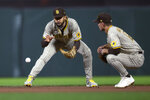 San Diego Padres shortstop Fernando Tatis Jr., left, fields a grounder by San Francisco Giants' Steven Duggar in front of second baseman Adam Frazier during the fourth inning of a baseball game, Tuesday, Sept. 14, 2021, in San Francisco. A runner was forced at second, and Duggar was safe at first. (AP Photo/D. Ross Cameron)
