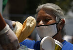 A woman gets a meal from the mobile dining rooms program as people who have not been able to work because of the COVID-19 pandemic line up for a meal outside the Iztapalapa hospital in Mexico City, Wednesday, May 20, 2020. (AP Photo/Marco Ugarte)