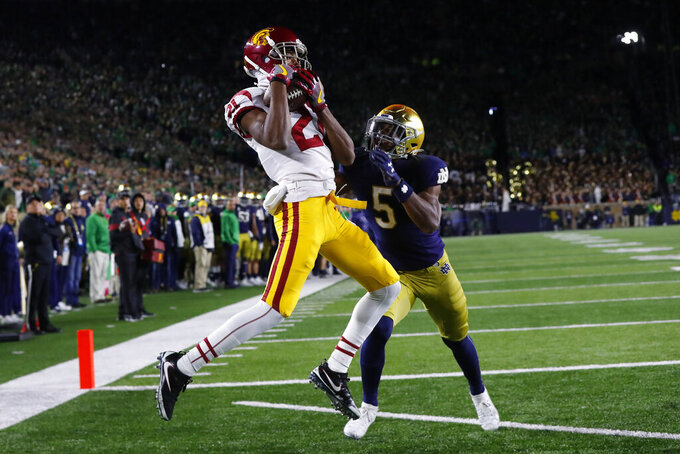 FILE - In this Oct. 12, 2019, file photo, Southern California wide receiver Tyler Vaughns (21) catches a 5-yard touchdown pass as Notre Dame cornerback Troy Pride Jr. (5) defends during the second half of an NCAA college football game in South Bend, Ind. USC and Notre Dame renew their storied rivalry in South Bend on Oct. 23. The Irish won their last meeting two years ago, 30-27. (AP Photo/Paul Sancya, File)