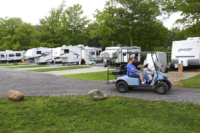 Marcia and Mike Vaughan drive their golf cart though the park, Monday, Aug. 3, 2020, at Hidden Creek Campground, just north of Peru, Indiana. (Tim Bath/The Kokomo Tribune via AP)