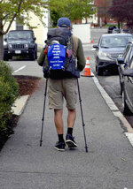 In this Wednesday, May 15, 2019 photo, U.S. Air Force veteran William Shuttlesworth walks up Market Street, in Newburyport, Mass., at the start of his planned cross-country hike to raise awareness for veterans' issues. Shuttleworth, 71, trained for several months carrying his full backpack while walking several miles each day. (Richard K. Lodge/The Daily News of Newburyport via AP)