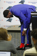 Carolina Panthers draft choice Brian Burns pulls up his pants leg to show off his Spiderman socks during a news conference for the NFL football team in Charlotte, N.C., Friday, April 26, 2019. (AP Photo/Chuck Burton)