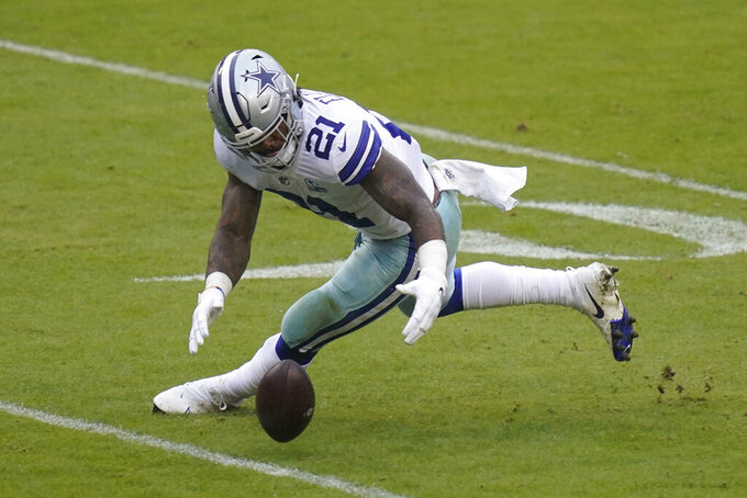 Dallas Cowboys running back Ezekiel Elliott (21) recovering a loose football during the second half of an NFL football game, Sunday, Oct. 25, 2020, in Landover, Md. (AP Photo/Patrick Semansky)