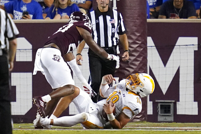 Kent State quarterback Collin Schlee (19) scores a touchdown after being knocked down by Texas A&M defensive back Caleb Surber (28) during the second half of an NCAA college football game on Saturday, Sept. 4, 2021, in College Station, Texas. (AP Photo/Sam Craft)