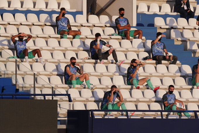 Real Madrid substitute players sit on the stands, observing social distancing to prevent the spread of coronavirus, prior to the Spanish La Liga soccer match between Leganes and Real Madrid at the Butarque Stadium in Leganes, on the outskirts of Madrid, Spain, Sunday, July 19, 2020. (AP Photo/Bernat Armangue)