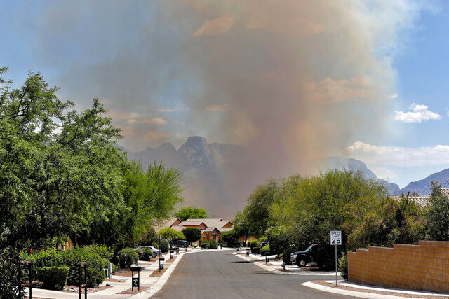 The Bighorn Fire backdrops a community along the western side of the Santa Catalina Mountains, Friday, June 12, 2020, in Tucson Ariz. Hundreds of homes on the outskirts of Tucson remain under an evacuation notice as firefighters work to keep the wildfire from moving downhill from canyons and ridges in the Coronado National Forest. (AP Photo/Matt York)