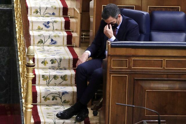 Spain's Prime Minister Pedro Sanchez listens to a speech by Vox party leader Santiago Abascal during a parliamentary session in Madrid, Spain, Wednesday Oct. 21, 2020. Spanish Prime Minister Pedro Sanchez faces a no confidence vote in Parliament put forth by the far right opposition party VOX. (AP Photo/Manu Fernandez, Pool)