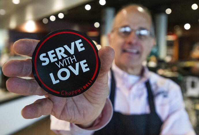 In this Feb. 7, 2020, photo, David Barranco shows car magnets he is giving out at his restaurant, Chappy's Deli, in Montgomery, Ala. In 2014, Chappy's won the River Region Ethics in Business and Public Service Award for its work in the community. The restaurant competed with the area's largest banks, law firms and other businesses for the award because Barranco's restaurants employed so many people. (Mickey Welsh/The Montgomery Advertiser via AP)