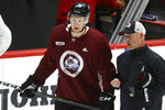 Colorado Avalanche center Nathan MacKinnon, left, confers with assistant coach Ray Bennett during an NHL hockey practice Monday, July 20, 2020, in Denver. (AP Photo/David Zalubowski)