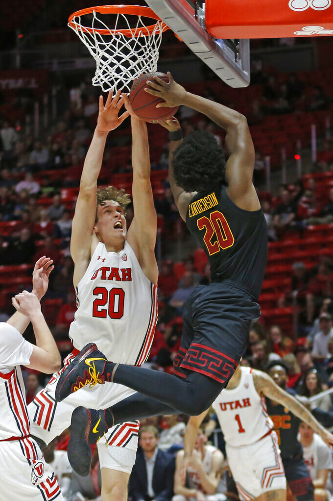 USC guard Ethan Anderson (20) goes to the basket as Utah forward Mikael Jantunen (20) defends in the first half of an NCAA college basketball game Sunday, Feb. 23, 2020, in Salt Lake City. (AP Photo/Rick Bowmer)