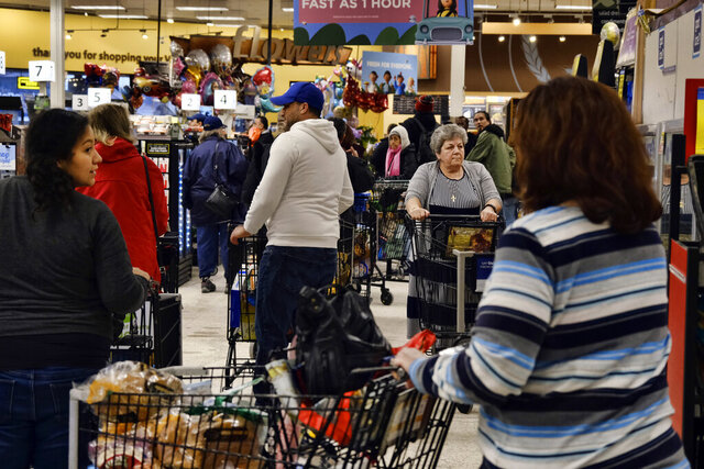 Shoppers crowd in long lines waiting to check out at a local Ralphs supermarket in an attempt to stock up on supplies, Friday, March 13, 2020, in the Panorama City section of Los Angeles. Officials said Friday the  Los Angeles Unified School District and San Diego school districts will close starting March 16 because of the coronavirus threat. The vast majority of people recover from the new coronavirus. According to the World Health Organization, most people recover in about two to six weeks, depending on the severity of the illness. (AP Photo/Richard Vogel)