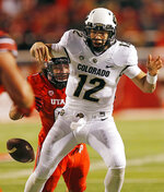 FILE - In this Nov. 25, 2017, file photo, Colorado quarterback Steven Montez (12) fumbles the ball as he is hit from behind by Utah defensive end Bradlee Anae during the second half during an NCAA college football game in Salt Lake City. Strong defensive lines are a trademark of Utah's football program. After experiencing a drop-off in production along the line of scrimmage a year ago, the Utes are focused on re-establishing their dominance up front this season. (AP Photo/Rick Bowmer)