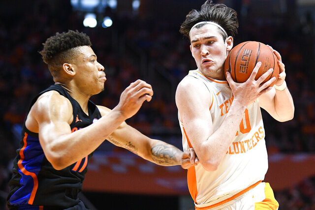 Tennessee forward John Fulkerson (10) dribbles the ball past Florida forward Keyontae Johnson (11)  during an NCAA college basketball game in Knoxville, Tenn., on Saturday, Feb. 29, 2020. (Calvin Mattheis/Knoxville News Sentinel via AP)