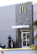 The McDonald's located on Lasalle Street in Mandeville, La., is about 100 yards from the shooting, is closed and guarded by a police officer Friday, Sept. 20, 2019. Two police officers have been shot in Louisiana, one fatally, after a vehicle chase north of New Orleans. The suspects are in custody. (David Grunfeld/The Advocate via AP)