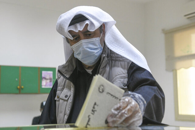 FILE - In this Saturday, Dec. 5, 2020 file photo, a man casts his vote for parliamentary elections in the town of Hawally, Kuwait. A new parliament has been elected in Kuwait in an election that saw two-thirds of lawmakers and the country's only female legislator lose their seats. Election results were released Sunday. (AP Photo/Jaber Abdulkhaleg, File)